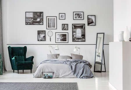 Photo for Grey bed between armchair and mirror in bedroom interior with gallery and lamps. Real photo - Royalty Free Image