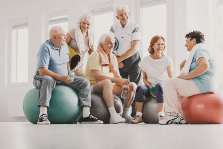 Photo pour Group of happy senior sitting on exercising balls in bright fitness center before training - image libre de droit