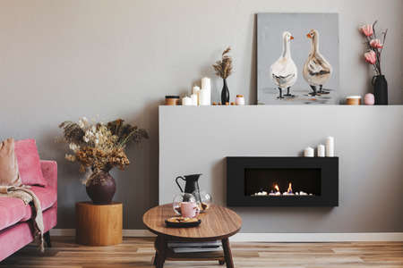Photo pour Elegant living room interior with black and grey fireplace, wooden coffee table and pink couch - image libre de droit
