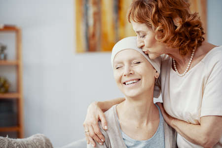 Photo pour Senior redhead woman kissing forehead of her happy best friend suffering from cervical cancer - image libre de droit