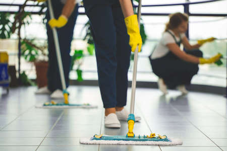 Foto de Close-up on person with yellow gloves holding mop while cleaning the floor - Imagen libre de derechos