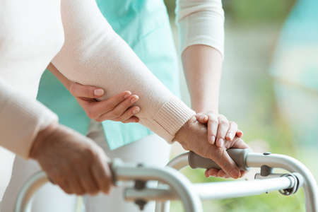 Photo pour Closeup of elderly lady's hands holding a walker and supporting nurse helping her - image libre de droit