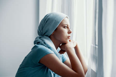 Foto per Thoughtful young girl suffering from bone cancer, wearing blue headscarf and looking through the window in hospital after surgery - Immagine Royalty Free