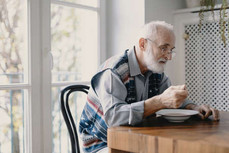 Foto de Senior grandfather with grey hair and beard sitting alone in the kitchen eating breakfast - Imagen libre de derechos