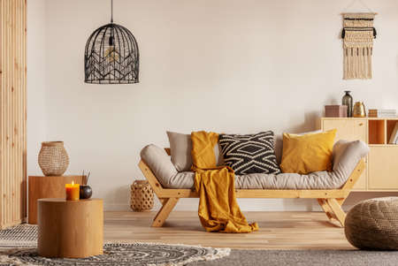 Foto de Scandinavian sofa with pillows and dark yellow blanket in bright living room interior with black chandelier - Imagen libre de derechos