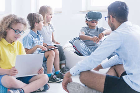 Photo pour Fascinated boy uses Virtual Reality glasses during technology lesson for children at innovative school - image libre de droit
