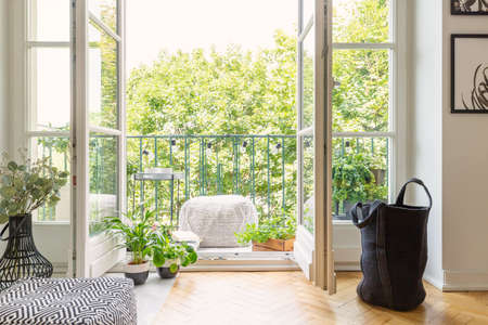 Foto de Real photo of open door to balcony with many fresh plants, lights, material pouf and view on urban jungle - Imagen libre de derechos