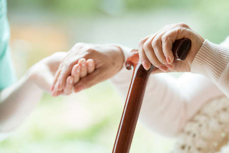 Foto de Closeup of senior grandmother holding walking cane in one hand and holding granddaughter's hand in the other - Imagen libre de derechos