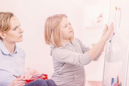Foto de Girl with autism doing exercises during meeting with psychotherapist - Imagen libre de derechos