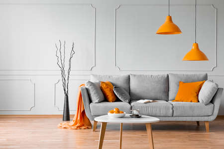 Photo pour Real photo of simple living room interior with orange lamps, pillows and grey sofa - image libre de droit