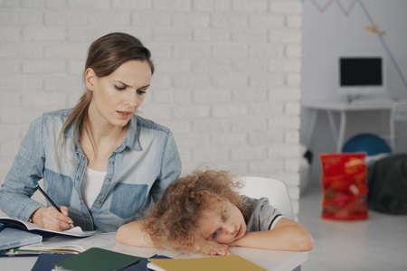 Foto de Worried teacher doing exercises with bored child during extra-curricular classes - Imagen libre de derechos