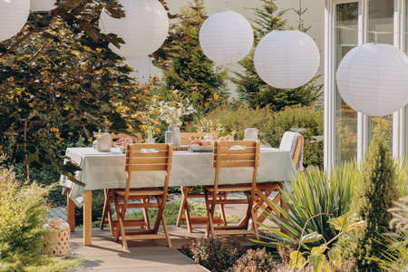 Photo pour Real photo of round lamps above a table with wooden chairs in a garden - image libre de droit
