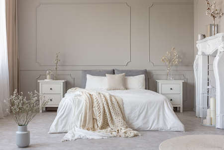 Foto de King size bed with white sheets and blanket between two wooden bedside tables flowers in vases - Imagen libre de derechos