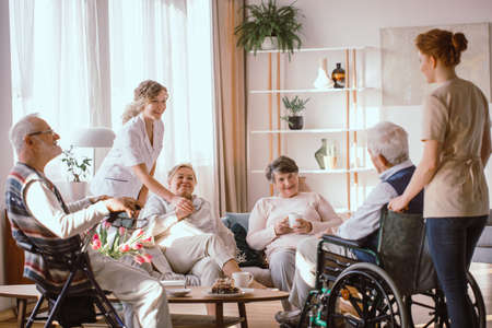 Photo pour Disabled grandparents spending time in common room with their caregivers - image libre de droit