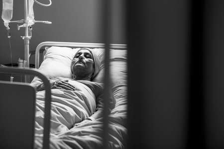 Foto de Black and white photo of Weak woman with cancer dying alone in hospital bed - Imagen libre de derechos