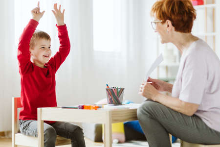 Foto de Cute little boy with ADHD during session with professional therapist - Imagen libre de derechos