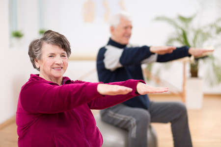 Foto de Elderly woman exercising during pilates for seniors in retirement home - Imagen libre de derechos