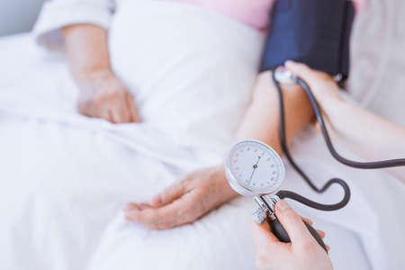 Foto de Closeup of senior woman with blood pressure monitor on her arm - Imagen libre de derechos