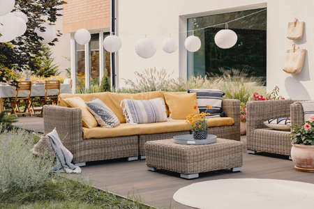 Photo pour Real photo of a rattan garden furniture set with lamps and table in the background - image libre de droit