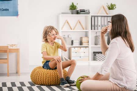 Foto de Happy autistic boy and professional therapist during treatment in the office - Imagen libre de derechos