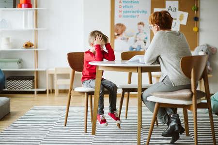 Foto de Cute little boy with ADHD during session with professional therapist - Imagen libre de derechos