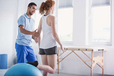 Photo pour Physiotherapist supporting woman during rehabilitation with ball - image libre de droit