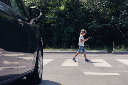 Photo for Low angle of car in front of pedestrian crossing and walking boy with smartphone - Royalty Free Image