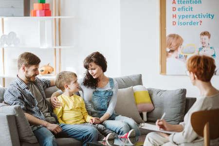 Foto de Caring parents and misbehaving boy during therapy session with counselor - Imagen libre de derechos