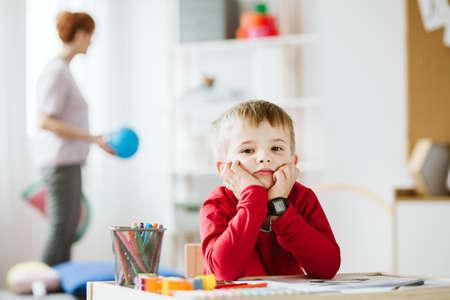 Foto de Cute little boy wearing red sweater sitting at small wooden table - Imagen libre de derechos
