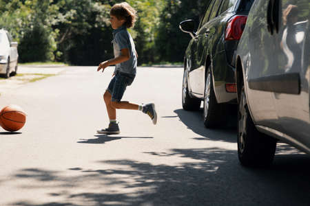 Photo for Careless boy running behind the ball on the road next to cars - Royalty Free Image