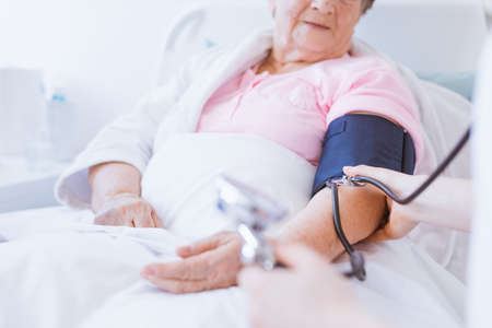 Foto per Senior woman with blood pressure monitor on her arm and young intern at hospital - Immagine Royalty Free