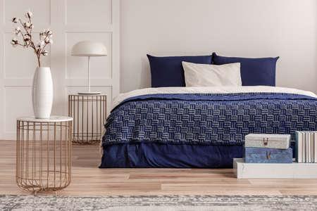 Foto de Flowers in vase on bedside table next to king size bed with navy blue bedding - Imagen libre de derechos