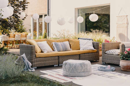 Photo for Pouf next to rattan couch and armchair on wooden terrace with flowers and lamps - Royalty Free Image