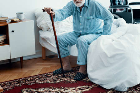 Foto de Old sick man with grey beard and hair wearing blue pajamas and sitting on bed at home - Imagen libre de derechos