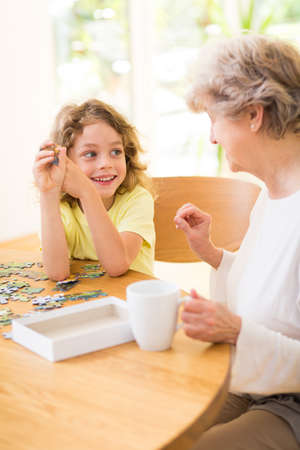 Photo for Boy and his grandmother assembling the puzzle together - Royalty Free Image
