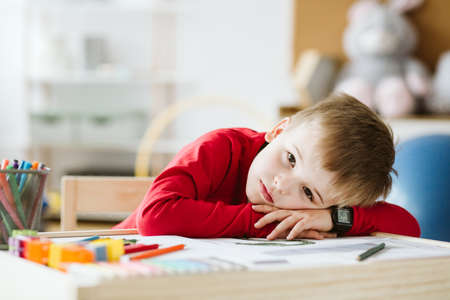 Photo pour Sad little boy in red sweater feeling lonely and lying on a table - image libre de droit