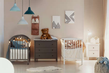 Foto de Real photo of a pastel bedroom interior for siblings with wooden cribs, beige walls, and cute teddy bears on a gray chest of drawers - Imagen libre de derechos