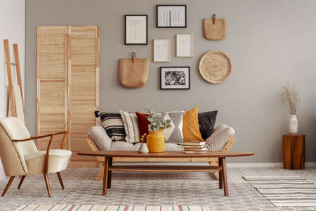 Photo pour Trendy creme colored armchair in Scandinavian living room interior with gallery of posters on beige wall - image libre de droit