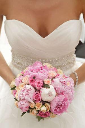 Foto de Beautiful wedding bouquet of pink and beige roses, paeonies in hands of the bride - Imagen libre de derechos