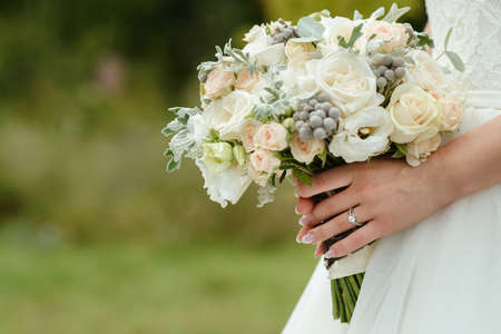 Foto de beautiful tender wedding bouquet of cream roses and eustoma flowers in hands of the bride - Imagen libre de derechos