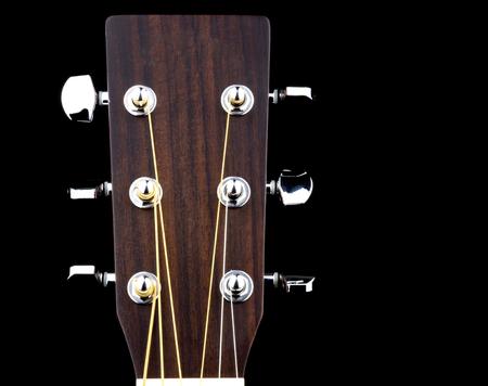 Photo pour Acoustic guitar peg head isolated against a black background - image libre de droit