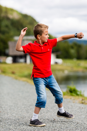 Photo for Boy throwing stone in the river on a sunny summer day in Norway. - Royalty Free Image
