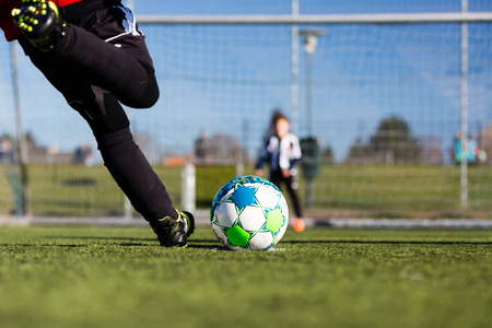 Photo pour Close-up of young soccer player taking a penalty kick against a young blurred boy acting as goalie in the goal. - image libre de droit