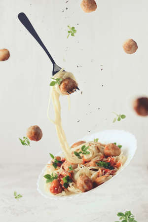 Photo for Flying food. Levitation of pasta fettuccine with meatballs, tomato sauce, basil on white concrete background - Royalty Free Image