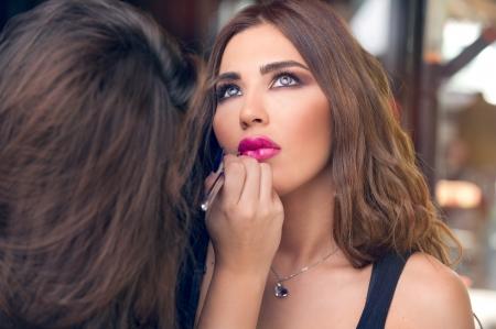 Photo pour Professional makeup artist applying make up on a beautiful young model s face   - image libre de droit