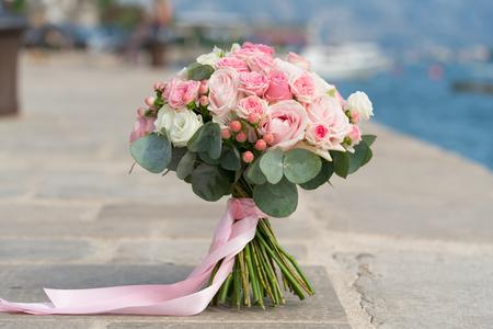 Foto de pink-white wedding bouquet stands on a pier near the sea, close up - Imagen libre de derechos