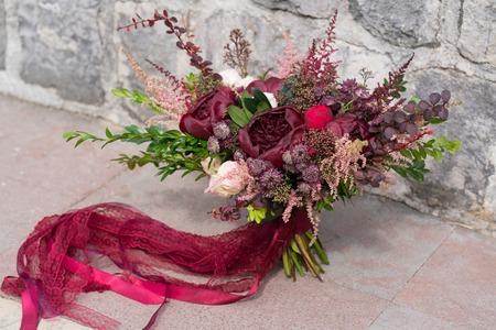 Foto de dark red wedding bouquet stands on stone wall background - Imagen libre de derechos