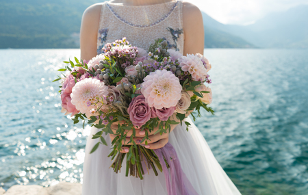 Foto de the bride holds a pink and lilac wedding bouquet in her arms against the background of the sea - Imagen libre de derechos