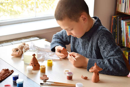 Photo pour Boy making ceramic toys, paints a pottery clay toy with gouache. Supporting creativity, learning by doing, DIY project, hand craft. Concept of education and development of gifted children - image libre de droit