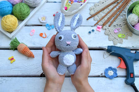 Foto de Making rabbit with carrot. Crochet bunny for child. On table threads, needles, hook, cotton yarn. Handmade crafts. DIY concept. Small business. Income from hobby - Imagen libre de derechos